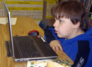 A young student uses a laptop computer.